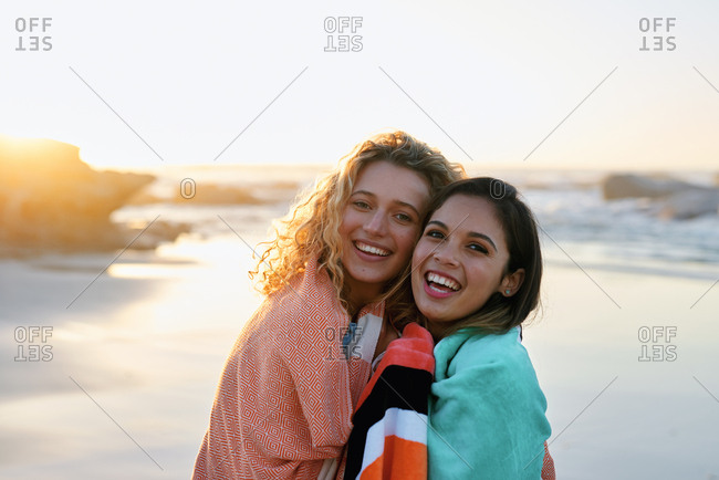 Best friends hugging on beach at sunset two beautiful women smiling happy enjoying friendship