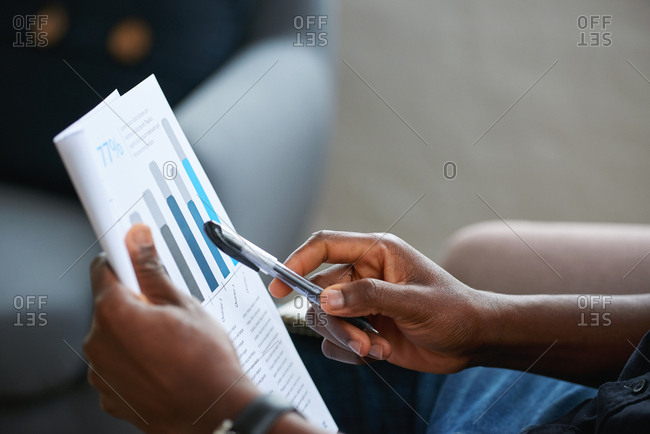 Businessman hand holding financial document with graph data planning marketing strategy looking at sales statistics