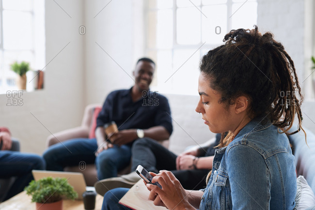 Young woman using smartphone browsing messages on social media texting on mobile phone sitting on sofa hanging out with friends
