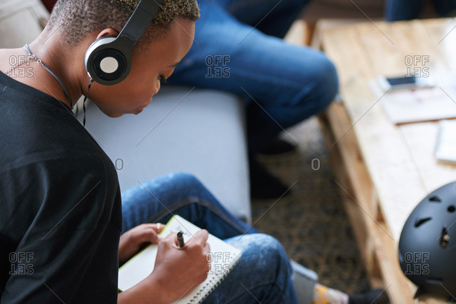 African american woman writing notes female student brainstorming listening to music wearing headphones