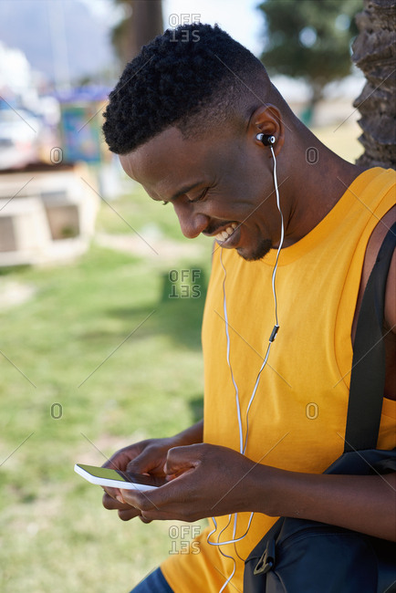 African american man using smartphone listening to music relaxing outdoors in park enjoying summer