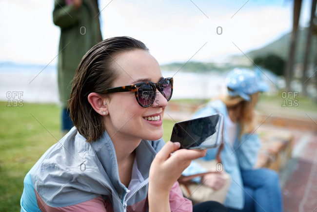 Beautiful woman using smartphone  on beachfront talking on mobile phone having conversation sharing summer vacation wearing sunglasses