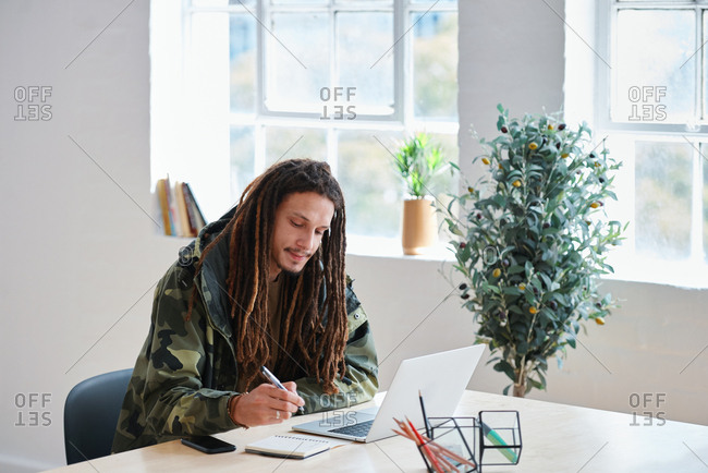 Young man with dreadlocks using laptop computer college student writing notes studying in class
