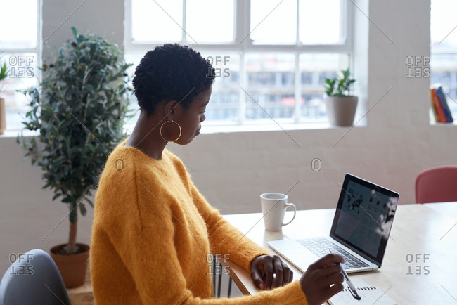 African american business woman using laptop computer working in home office wearing yellow jersey