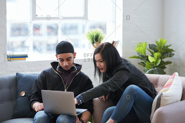 Friends using laptop computer browsing online young woman pointing at screen students working on project sitting on sofa at home