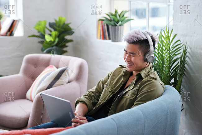Young asian man using tablet computer watching entertainment listening to music wearing headphones on mobile device relaxing at home on sofa