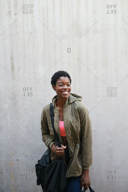 Portrait attractive african american woman smiling independent black female with concrete wall background