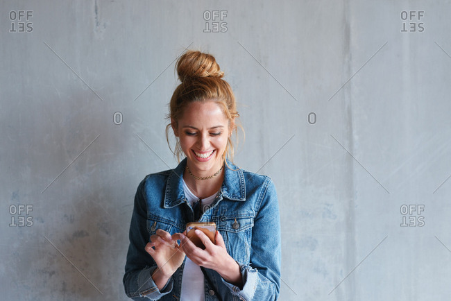 Portrait young redhead woman using smartphone texting browsing social media messages smiling happy by concrete wall in city
