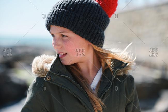 Portrait little girl smiling happy on seaside dressed warm wearing beanie hat and coat