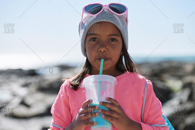 Portrait of little girl drinking milkshake on beach having fun summer vacation