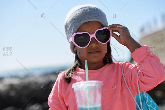 Portrait of little girl drinking milkshake on beach wearing sunglasses having fun summer vacation