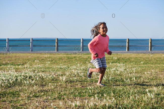 Little girl running in park by seaside playful child enjoying childhood freedom