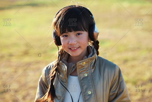 Cute little asian girl wearing headphones listening to music in park