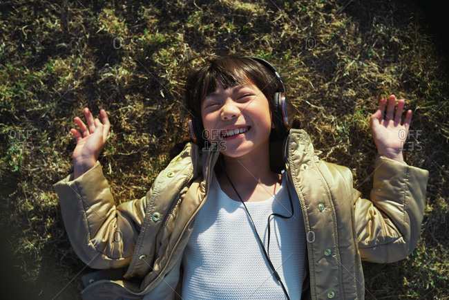 Funny little asian girl wearing headphones lying on grass laughing having fun listening to music in park