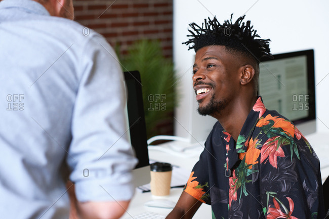 Happy african american man talking to colleague in office smiling happy wearing Hawaiian shirt