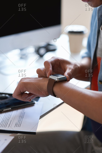 Man hands using smart watch wearable mobile technology in office