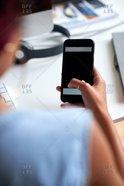 Young woman using smartphone in office browsing messages on mobile phone