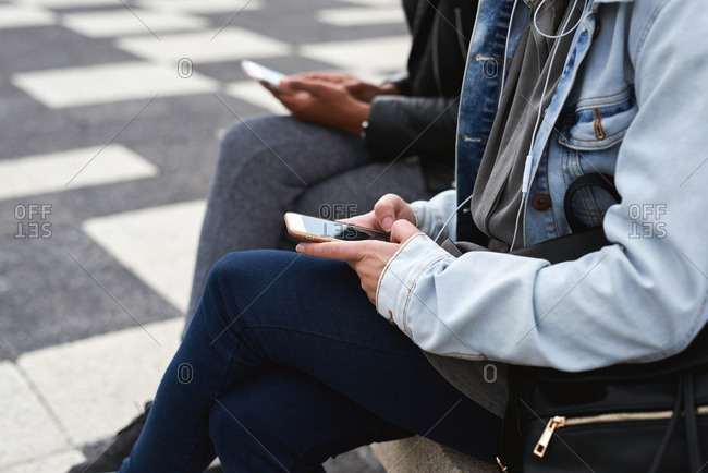 Woman using smartphone sitting on bench in city texting on mobile phone