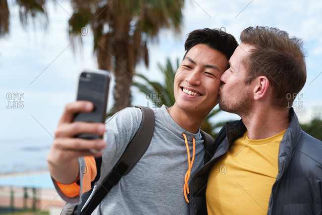 Happy homosexual couple taking photo using smartphone young man kissing partner on cheek sharing romantic date on social media