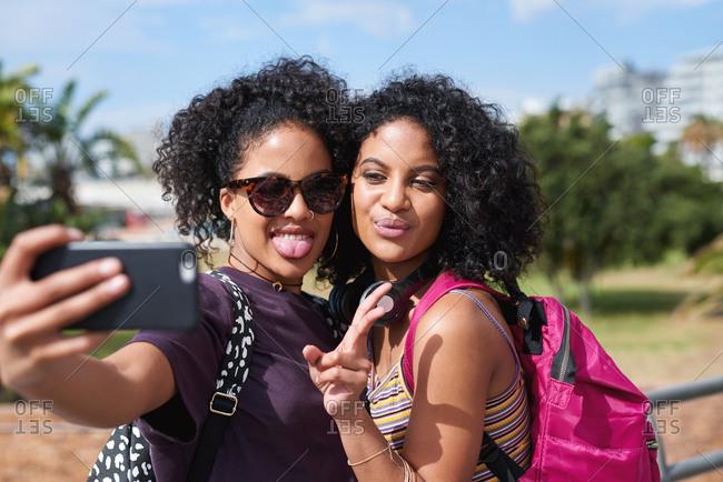 Beautiful twin sisters posing taking selfie photo using smartphone having fun summer vacation sharing travel on mobile phone social media