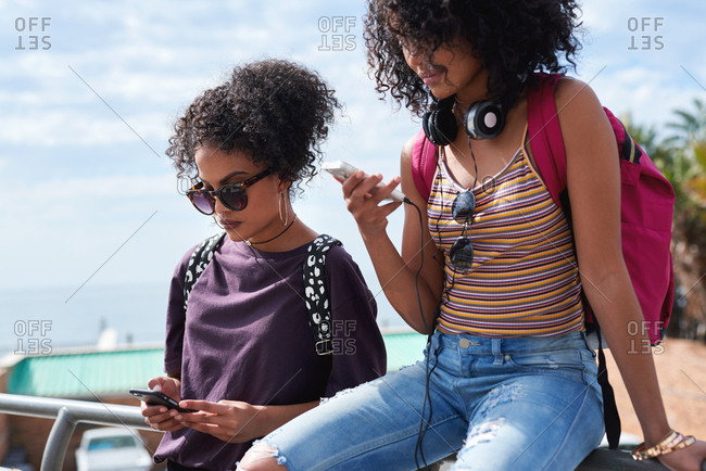 Twin sisters using smartphones in city relaxing on summer day browsing social media texting on mobile phones