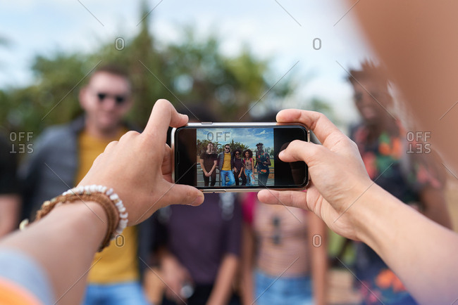 Friends posing for photo with hands holding smartphone photographing travel people with mobile phone camera pov