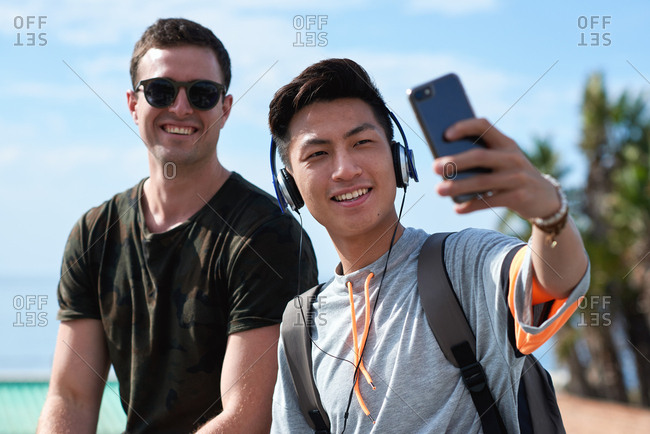 Best friends taking selfie photo on beach using smartphone guys hanging out by seaside sharing fun on social media with mobile phone