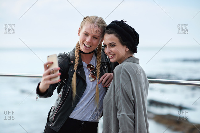 Best friends taking selfie photo using smartphone on seaside hanging out sharing fun on social media with mobile phone