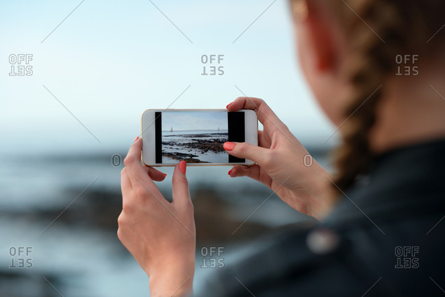 Woman using smartphone taking photo of sea female tourist on vacation photographing scenic view with mobile phone camera