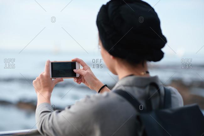 Woman using smartphone taking photo of sea female tourist on vacation