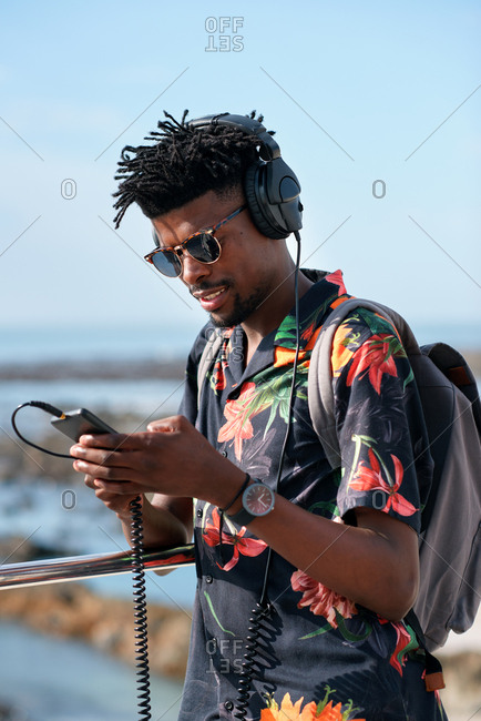 African american travel man using smartphone on beach with mobile phone sharing summer vacation wearing headphones listening to music