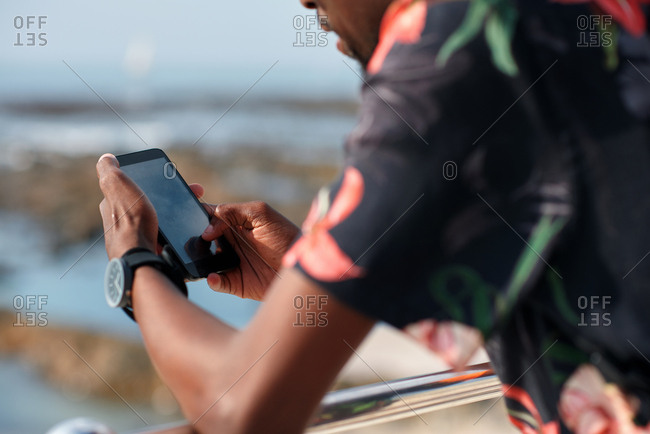 African american travel man using smartphone on beach texting with mobile phone sharing summer vacation wearing colorful Hawaiian shirt
