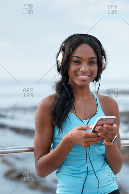 Young african american woman using smartphone on beach female jogger listening to music wearing headphones relaxing by the sea
