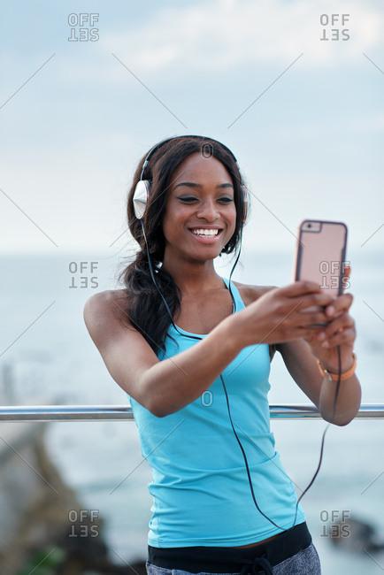 Happy african american woman taking selfie photo using smartphone camera on beach female jogger listening to music wearing headphones