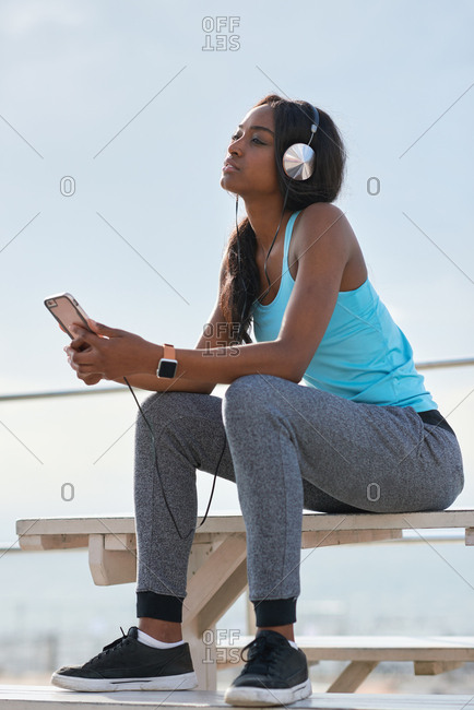 Young african american woman using smartphone on beach female jogger listening to music wearing headphones sitting on bench relaxing by the sea