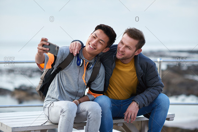 Happy homosexual couple taking photo on beach using smartphone sharing romantic vacation together on social media with mobile phone
