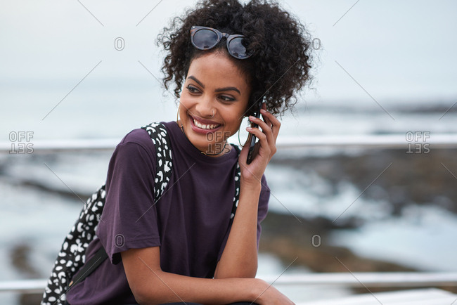 Beautiful hispanic woman using smartphone talking on mobile phone call conversation by the beach smiling happy