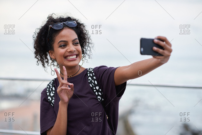 Happy woman taking selfie photo using smartphone camera on beach smiling excited making peace sign with hand sharing travel vacation on social media