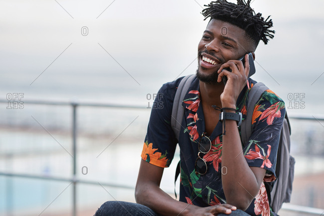 African american man using smartphone talking on mobile phone call conversation by the beach