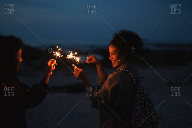 Twin sisters celebrating with sparklers on new years eve having fun on beach at night