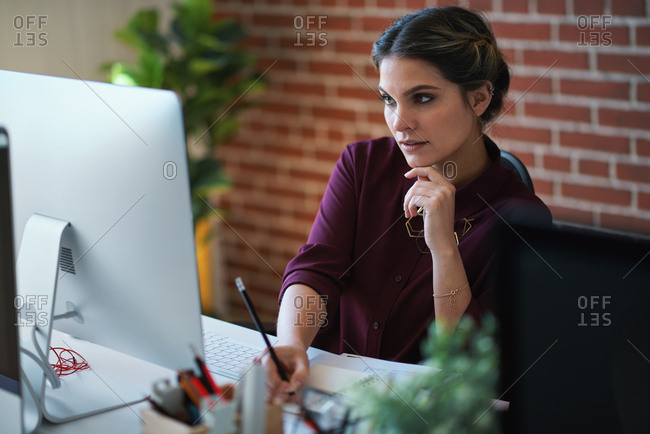 Business woman using computer in office brainstorming female entrepreneur thinking of creative ideas planning strategy looking pensive witting in notebook