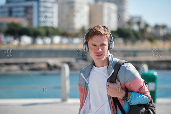Portrait young redhead man wearing headphones listening to music on waterfront beach looking confident teenager summertime fashion
