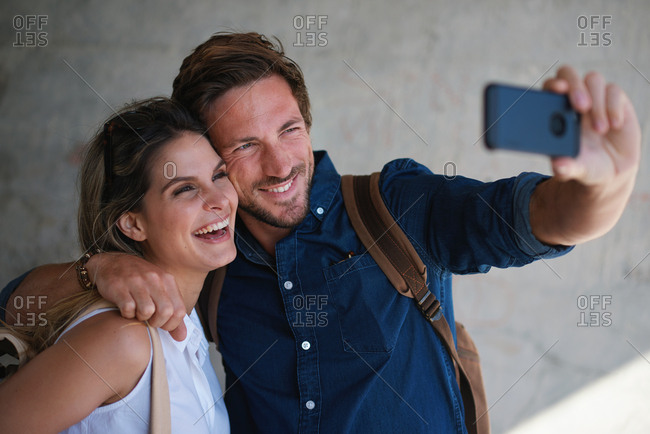 Happy couple taking photos using smartphone camera sharing vacation together on mobile phone social media having fun summertime