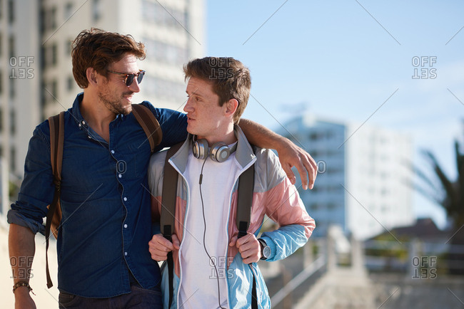 Young man embracing friend in city best friends bonding enjoying friendship