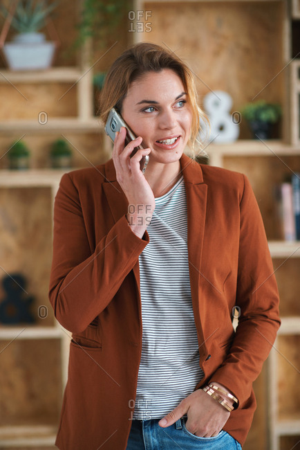 Successful businesswoman using smartphone talking on mobile phone having conversation in office