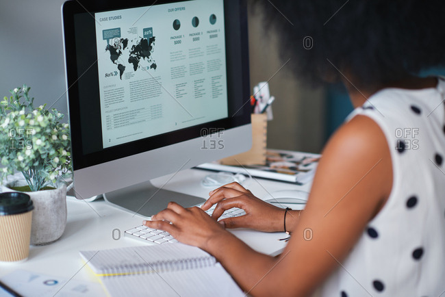 African american business woman using computer in office with financial data on screen
