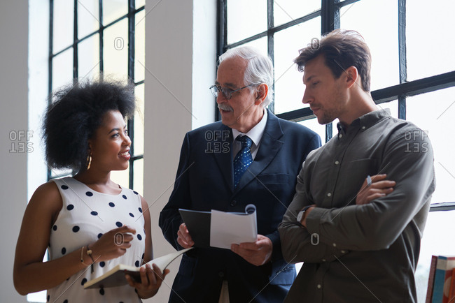 Senior businessman meeting colleagues discussing business documents with boss in office