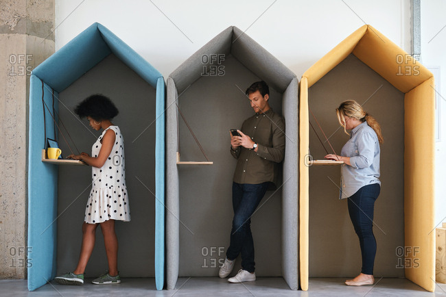 Business people working in colorful office cubicles in workplace