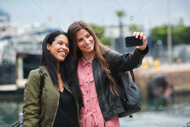 Best friends taking photo together using smartphone camera at the harbor