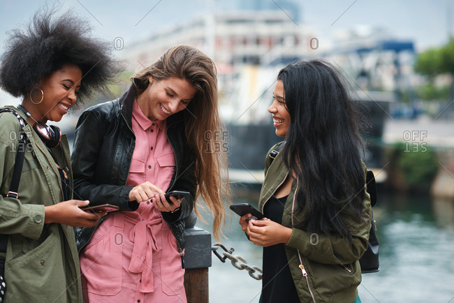 Multiracial friends using smartphone browsing text messages in waterfront group of women sharing gossip on social media with mobile phone technology